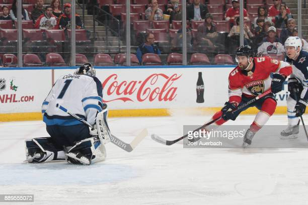 Goaltender Eric Comrie of the Winnipeg Jets stops a shot by Aaron Ekblad of the Florida Panthers at the BBT Center on December 7 2017 in Sunrise...