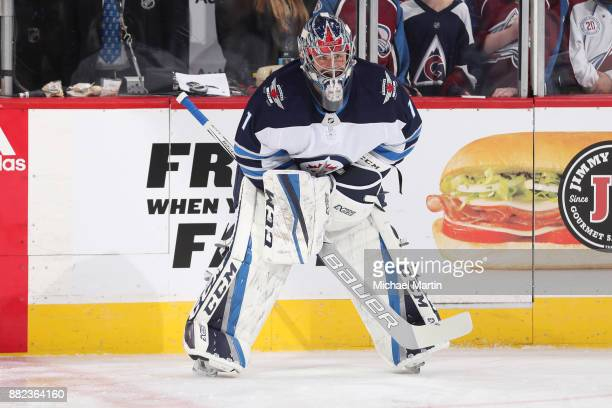 Goaltender Eric Comrie of the Winnipeg Jets stretches during warm ups prior to the game against the Colorado Avalanche at the Pepsi Center on...
