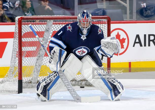 Goaltender Eric Comrie of the Winnipeg Jets takes part in the pregame warm up prior to NHL action against the Boston Bruins at the Bell MTS Place on...