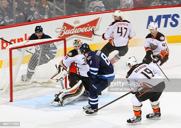 Goaltender Frederik Andersen of the Anaheim Ducks looks behind him as the puck shot by Jacob Trouba of the Winnipeg Jets rolls toward the net for a...