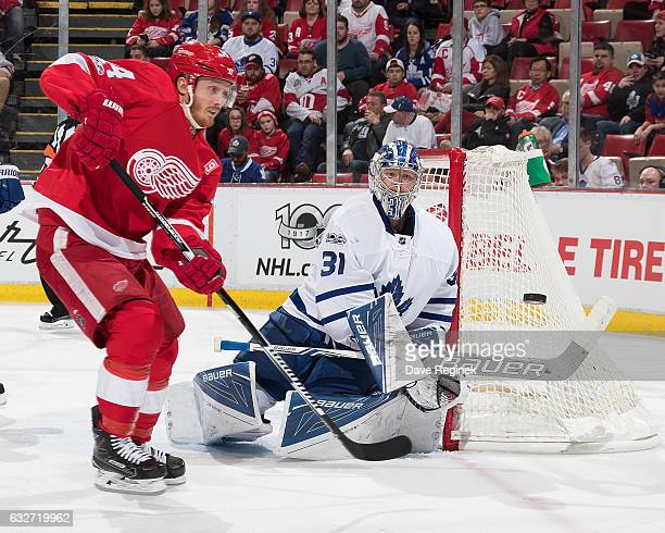 Goaltender Frederik Andersen of the Toronto Maple Leafs bats the puck away as Gustav Nyquist of the Detroit Red Wings look for the rebound during an...