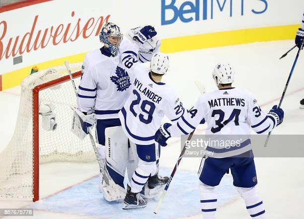 Goaltender Frederik Andersen of the Toronto Maple Leafs gets congratulations from teammates William Nylander and Auston Matthews following a 72...