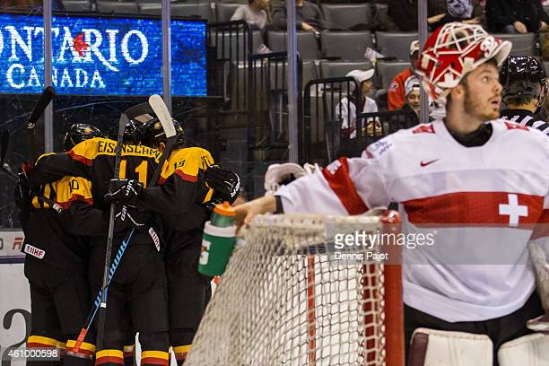 Goaltender Gauthier Descloux of Switzerland reaches for the water bottle as Markus Eisenschmid of Germany celebrates a goal during the 2015 IIHF...