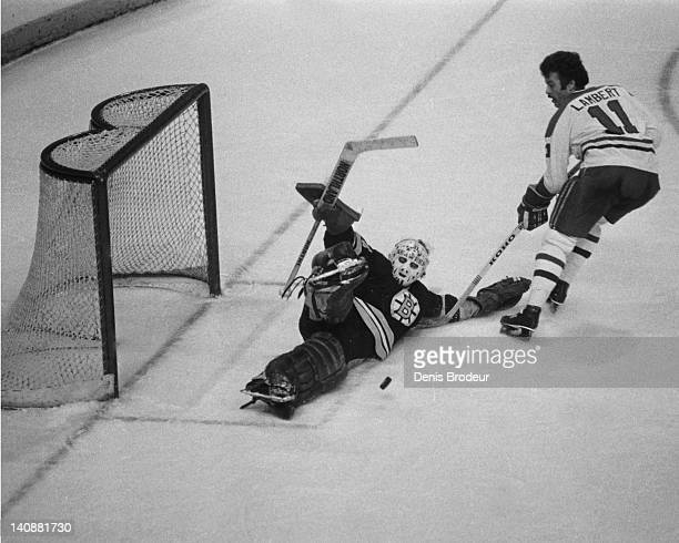 Goaltender Gerry Cheevers of the Boston Bruins makes a diving save on Yvon Lambert of the Montreal Canadiens on a breakaway Circa 1970 at the...