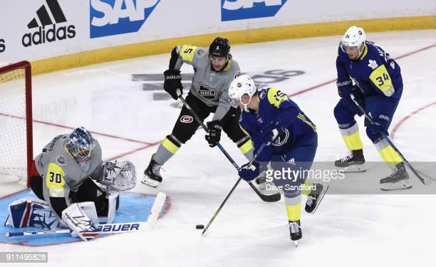 Goaltender Henrik Lundqvist of the New York Rangers defends his net against Jack Eichel of the Buffalo Sabres as Auston Matthews of the Toronto Maple...