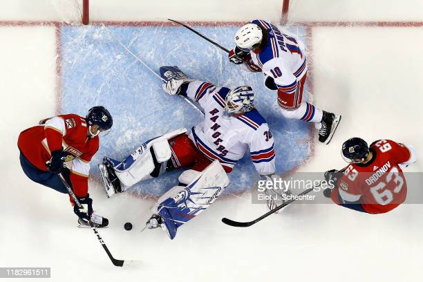 Goaltender Henrik Lundqvist of the New York Rangers defends the net with the help of teammate Artemi Panarin against Jonathan Huberdeau and Evgeni...