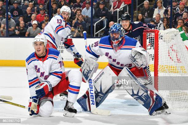 Goaltender Henrik Lundqvist of the New York Rangers defends the net against the Columbus Blue Jackets with the help of Brady Skjei of the New York...