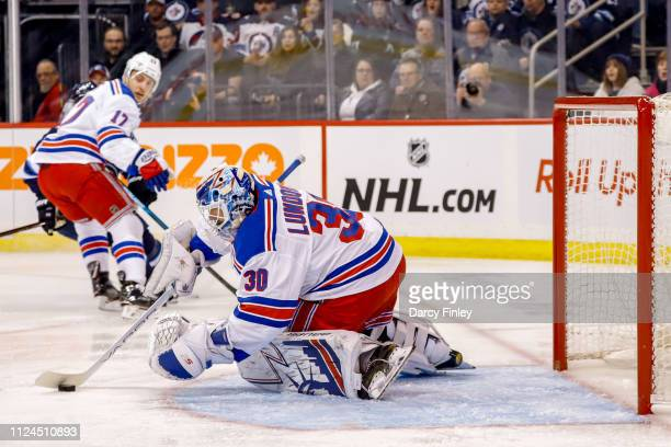 Goaltender Henrik Lundqvist of the New York Rangers gathers up the loose puck during first period action against the Winnipeg Jets at the Bell MTS...