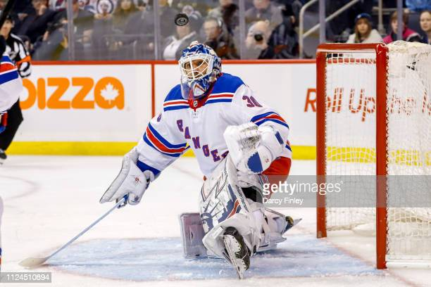 Goaltender Henrik Lundqvist of the New York Rangers keeps an eye on the flying puck during first period action against the Winnipeg Jets at the Bell...