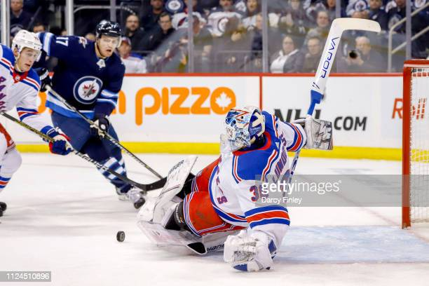 Goaltender Henrik Lundqvist of the New York Rangers makes a sliding pad save during first period action against the Winnipeg Jets at the Bell MTS...