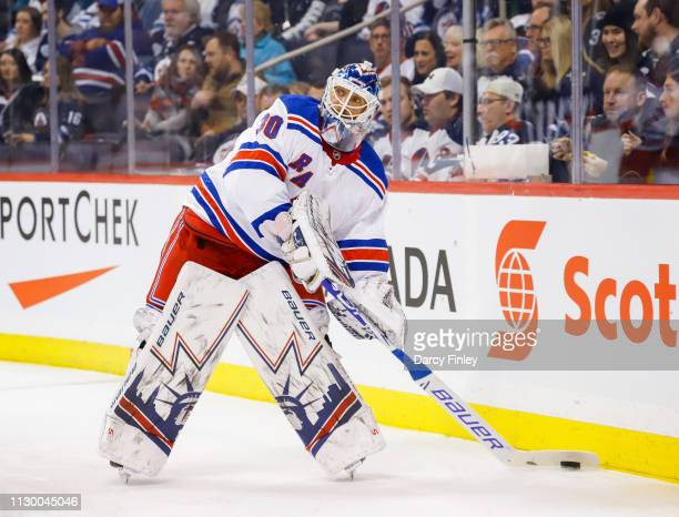 Goaltender Henrik Lundqvist of the New York Rangers plays the puck along the boards during first period action against the Winnipeg Jets at the Bell...