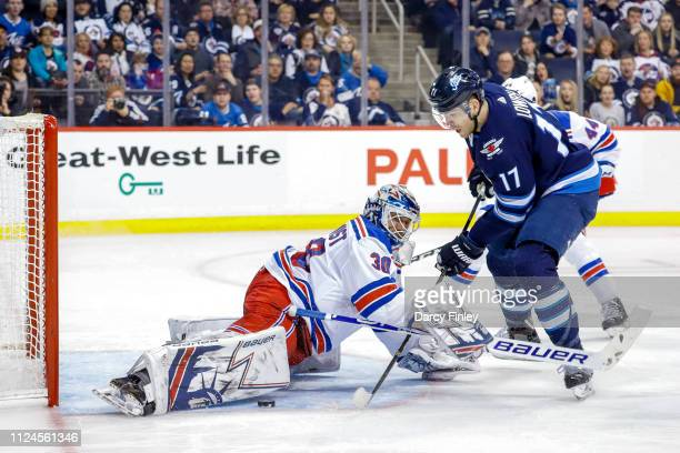 Goaltender Henrik Lundqvist of the New York Rangers stretches out a pad as he makes a save on Adam Lowry of the Winnipeg Jets during second period...
