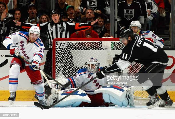 Goaltender Henrik Lundqvist of the New York Rangers watches as Anze Kopitar of the Los Angeles Kings reaches for the puck against Ryan McDonagh in...