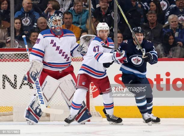 Goaltender Henrik Lundqvist Steven Kampfer of the New York Rangers and Mark Scheifele of the Winnipeg Jets keep an eye on the play during first...