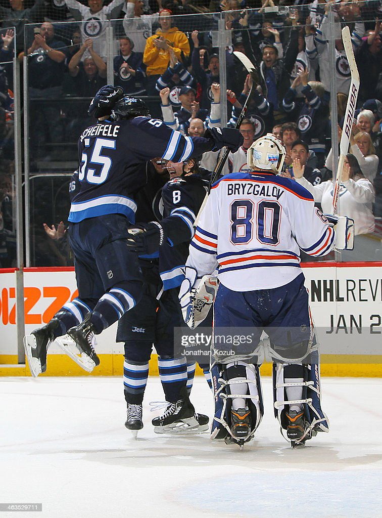 Goaltender Ilya Bryzgalov #80 of the Edmonton Oilers skates off the ice as Mark Scheifele #55 of the Winnipeg Jets jumps on teammates Blake Wheeler #26 and Jacob Trouba #8 to celebrate an overtime goal at the MTS Centre on January 18, 2014 in Winnipeg, Manitoba, Canada. The Jets defeated the Oilers 3-2.