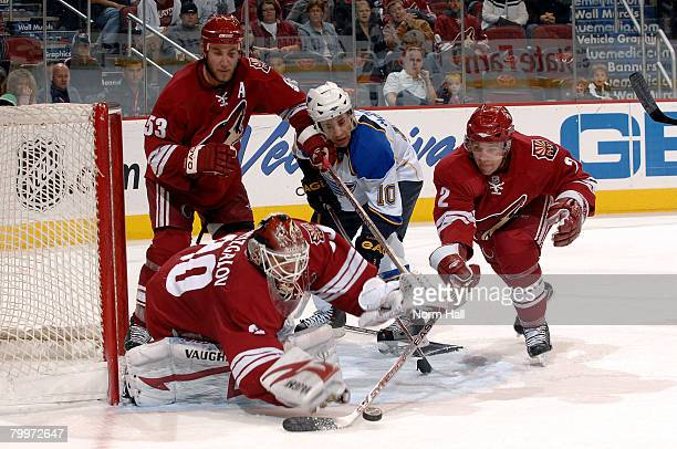 Goaltender Ilya Bryzgalov of the Phoenix Coyotes dives for a loose puck as teammate Keith Ballard gets his stick on it while coyotes defenseman Derek...