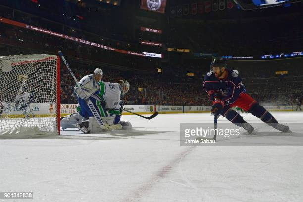 Goaltender Jacob Markstrom of the Vancouver Canucks defends the net as Nick Foligno of the Columbus Blue Jackets skates with the puck during the...