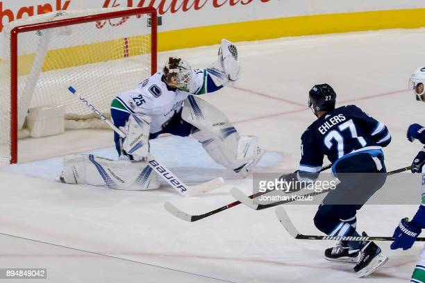 Goaltender Jacob Markstrom of the Vancouver Canucks makes a glove save off a shot by Nikolaj Ehlers of the Winnipeg Jets during third period action...
