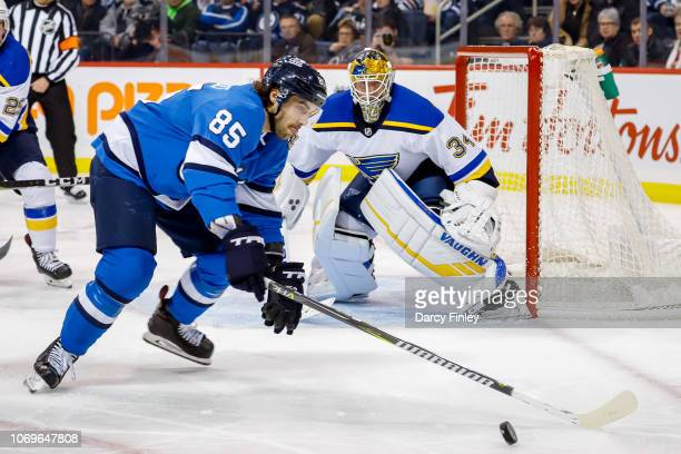 Goaltender Jake Allen of the St Louis Blues keeps an eye on Mathieu Perreault of the Winnipeg Jets as he plays the puck to the side of the net during...