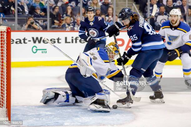 Goaltender Jake Allen of the St Louis Blues makes a pad save as Mathieu Perreault of the Winnipeg Jets looks for the rebound during second period...