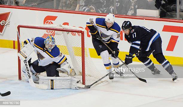 Goaltender Jake Allen of the St Louis Blues makes a skate save against the post as Adam Lowry of the Winnipeg Jets tries to score during second...