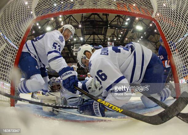 Goaltender James Reimer and defensemen Mike Kostka and Carl Gunnarsson of the Toronto Maple Leafs manage to stop Kyle Okposo of the New York...
