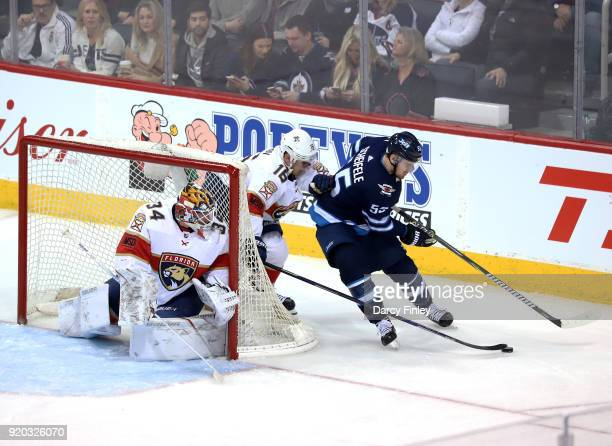 Goaltender James Reimer watches as Mark Scheifele of the Winnipeg Jets plays the puck away from Aleksander Barkov behind the net during second period...