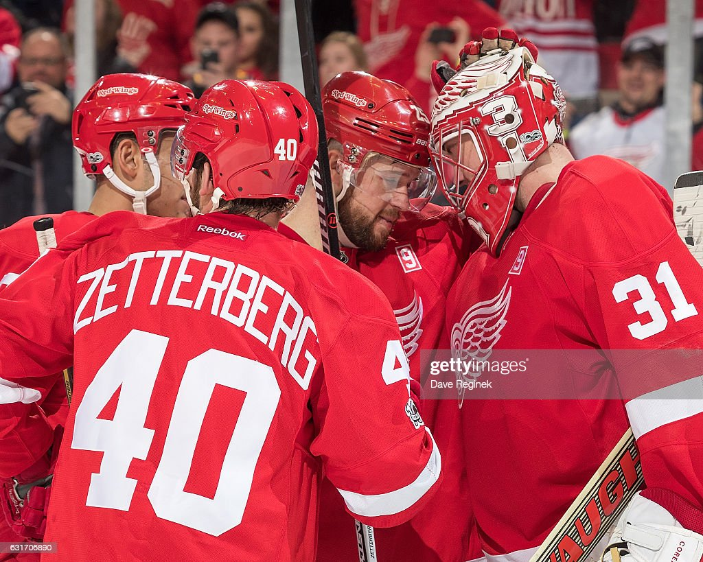 Goaltender Jared Coreau #31 of the Detroit Red Wings is congratulated by teammates Mike Green #25, Andreas Athanasiou #72 and Henrik Zetterberg #40 on the win following an NHL game against the Pittsburgh Penguins at Joe Louis Arena on January 14, 2017 in Detroit, Michigan. The Wings defeated the Penguins 6-3.