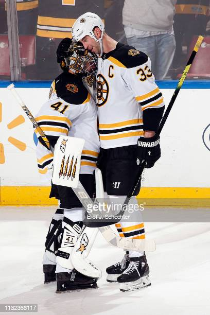 Goaltender Jaroslav Halak of the Boston Bruins gets a hug from teammate Zdeno Chara after their 73 win over the Florida Panthers at the BBT Center on...