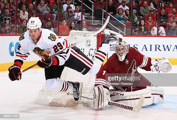 Goaltender Jason LaBarbera of the Phoenix Coyotes follows the action as Bryan Bickell of the Chicago Blackhawks is tripped up during the third period...