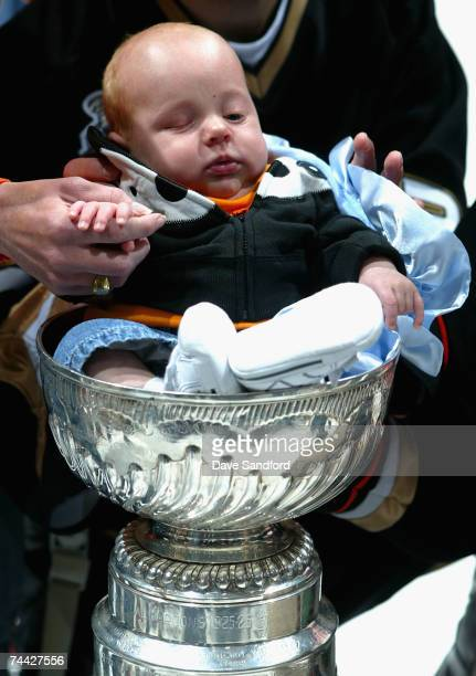 Goaltender JeanSebastien Giguere of the Anaheim Ducks holds his infant son Maxime in the Stanley Cup after defeating the Ottawa Senators in Game Five...