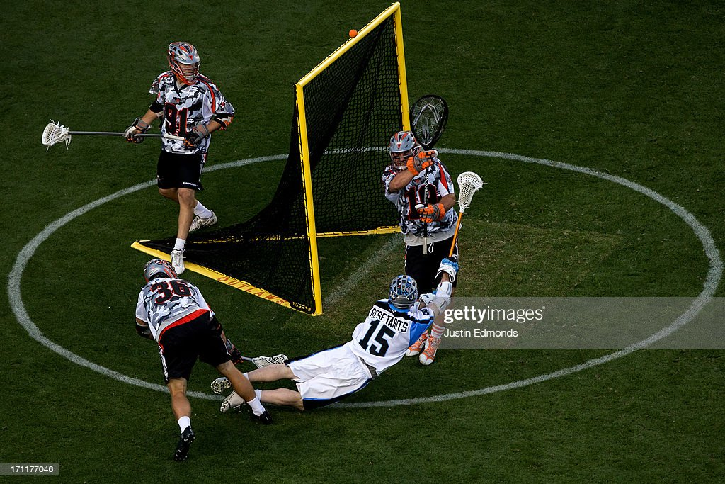Goaltender Jesse Schwartzman #19 of the Denver Outlaws makes a save on Joe Resetarits #15 of the Ohio Machine as Landon Carr #36 and Dillon Roy #91 defend during the second quarter at Sports Authority Field at Mile High on June 22, 2013 in Denver, Colorado.