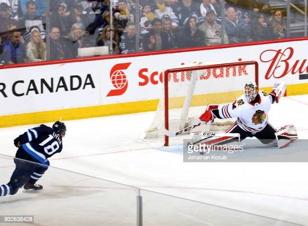 Goaltender JF Berube of the Chicago Blackhawks slides across the crease to make a pad stop on a shot by Bryan Little of the Winnipeg Jets during...