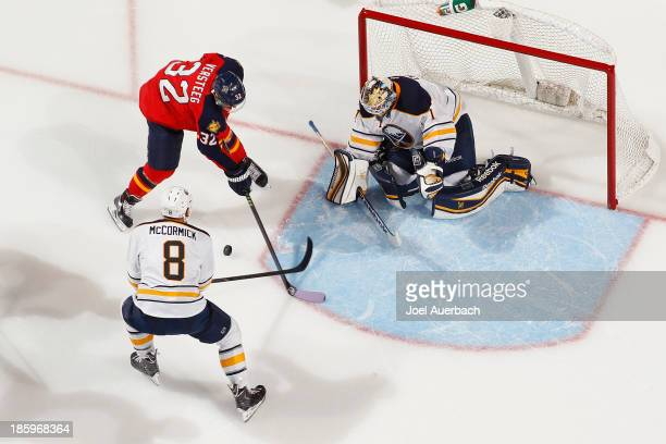 Goaltender Jhonas Enroth defends the net as Cody McCormick of the Buffalo Sabres knocks the puck off the stick of Kris Versteeg of the Florida...