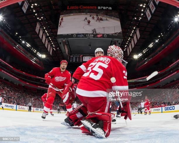 Goaltender Jimmy Howard of the Detroit Red Wings follows the puck as teammate Jonathan Ericsson defends against Matt Niskanen of the Washington...