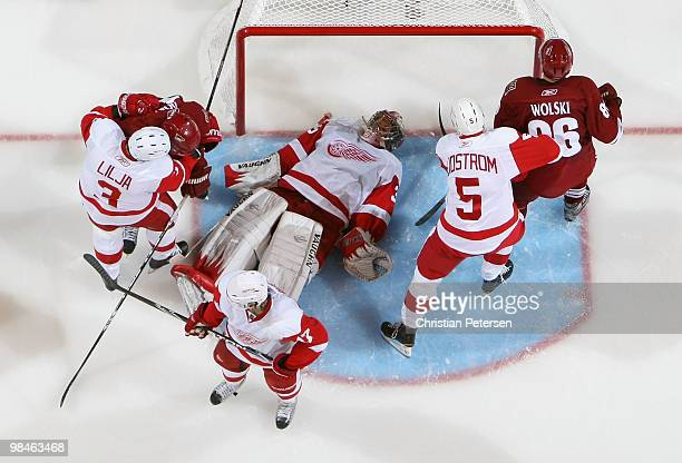 Goaltender Jimmy Howard of the Detroit Red Wings lays on the puck in the crease after making a save against the Phoenix Coyotes in Game One of the...