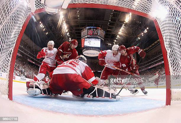 Goaltender Jimmy Howard of the Detroit Red Wings makes a pad save on the puck as Martin Hanzal and Petr Prucha of the Phoenix Coyotes battle for a...