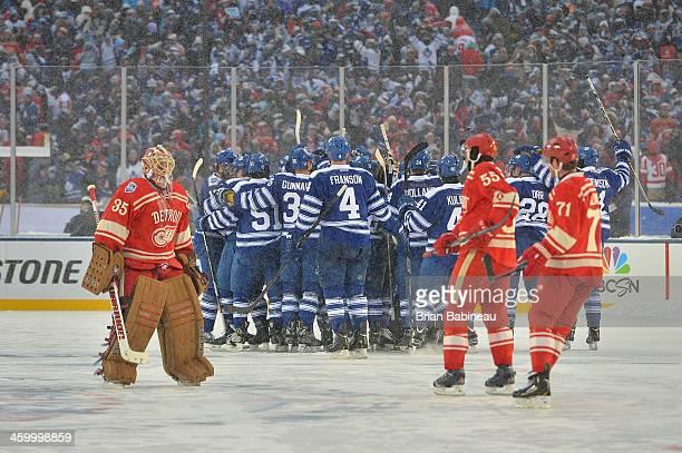 Goaltender Jimmy Howard of the Detroit Red Wings skates toward the Wings bench as teammates Niklas Kronwall and Daniel Cleary skate to meet Howard as...