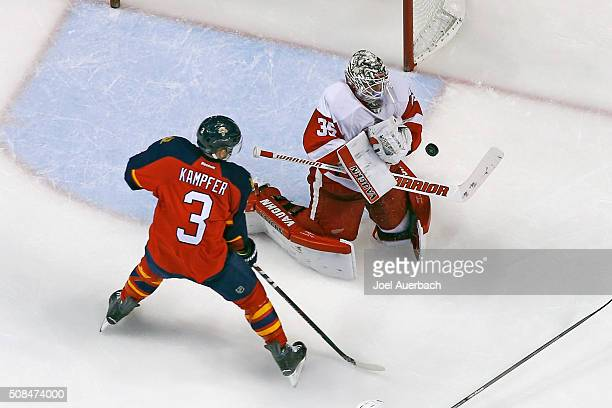 Goaltender Jimmy Howard of the Detroit Red Wings stops a shot with Steve Kampfer of the Florida Panthers waiting for a rebound at the BBT Center on...