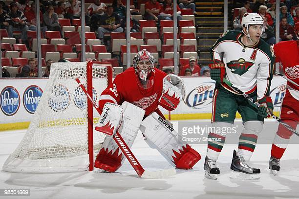 Goaltender Jimmy Howard of the Detroit Red Wings watches for a shot as Andrew Brunette of the Minnesota Wild waits for a deflection during their NHL...