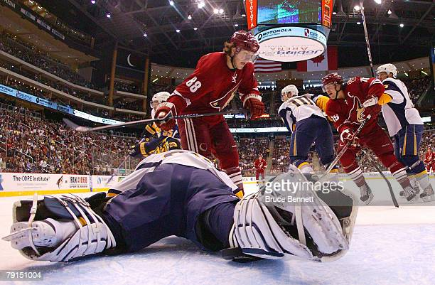 Goaltender Jocelyn Thibault of the Buffalo Sabres defends against Peter Mueller and Shane Doan of the Phoenix Coyotes on January 21 2008 at the...