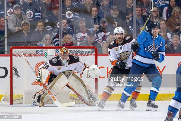 Goaltender John Gibson Adam Henrique of the Anaheim Ducks and Mark Scheifele of the Winnipeg Jets keep an eye on the play at the point during first...