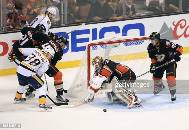 Goaltender John Gibson of the Anaheim Ducks defends the centering pass by James Neal of the Nashville Predators from behind the net in the first...