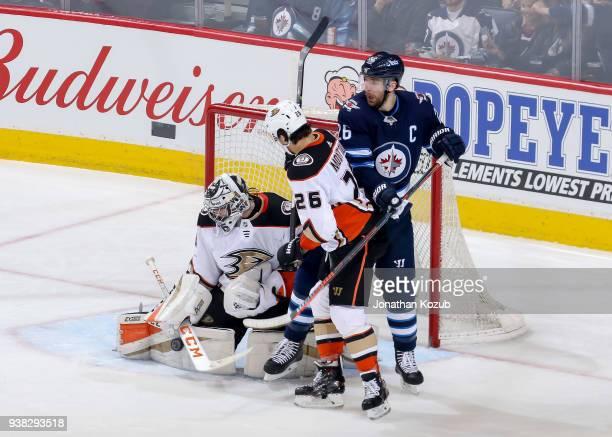 Goaltender John Gibson of the Anaheim Ducks makes a save as teammate Brandon Montour battles Blake Wheeler of the Winnipeg Jets in the crease during...