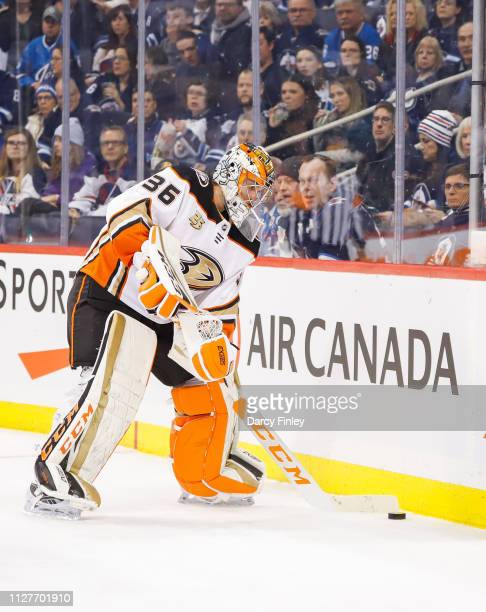 Goaltender John Gibson of the Anaheim Ducks plays the puck along the boards during first period action against the Winnipeg Jets at the Bell MTS...