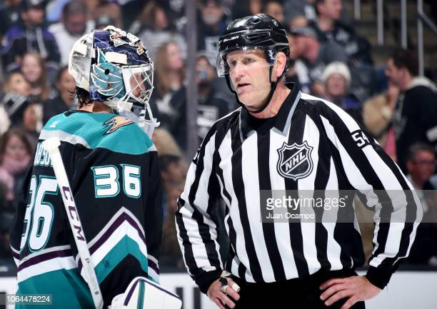 Goaltender John Gibson of the Anaheim Ducks talks with linesman Greg Devorski during the first period of the game against the Los Angeles Kings at...