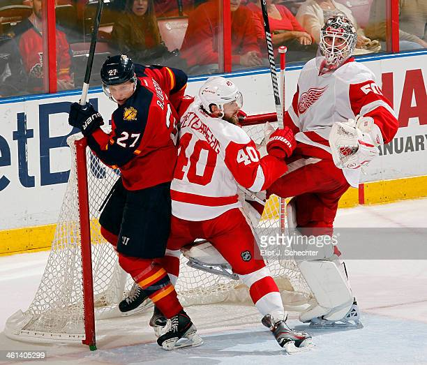 Goaltender Jonas Gustavsson of the Detroit Red Wings defends the net with the help of teammate Henrik Zetterberg against Nick Bjugstad of the Florida...