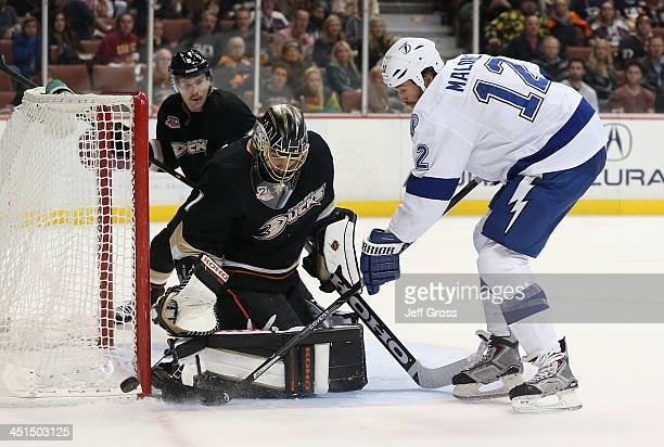Goaltender Jonas Hiller of the Anaheim Ducks defends his net as Ryan Malone of the Tampa Bay Lightning pokes at the puck in the second period at...