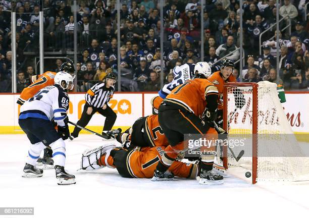 Goaltender Jonathan Bernier of the Anaheim Ducks stretches in the crease as the puck trickles over the goal line on a deflection by Dustin Byfuglien...