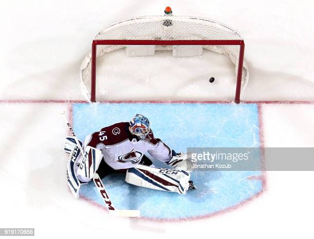 Goaltender Jonathan Bernier of the Colorado Avalanche looks back as a slapshot from the stick of Patrik Laine of the Winnipeg Jets gets past him for...